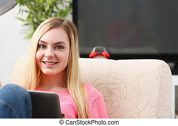 young beautiful blond woman sit on the sofa in livingroom hold tablet in arms