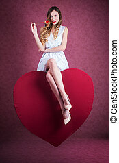 Young beautiful blond woman sitting on a giant heart
