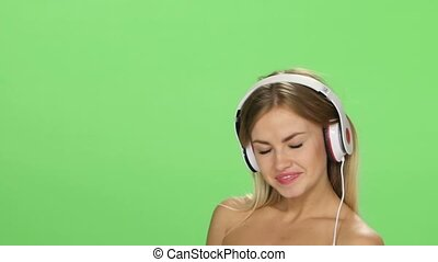 Young beautiful blonde girl dancing with headphones isolated on a green screen