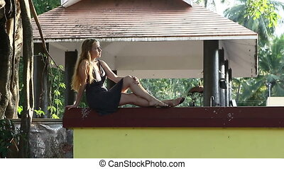 young beautiful blonde girl - girl sitting on the fence near...
