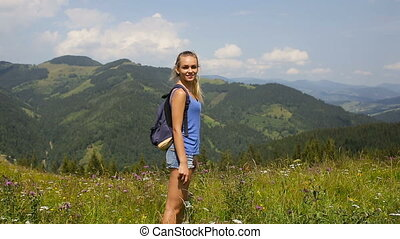 Young beautiful blonde girl posing in the mountains on a background of clouds
