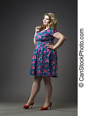 Young beautiful blonde plus size model in dress and shoes, xxl woman on gray studio background