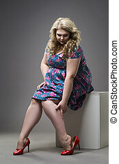 Young beautiful blonde plus size model in red high heels...