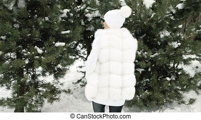 Young beautiful blonde walk among trees like on catwalk.