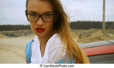 young beautiful blonde with red lips wears a glasses posing on camera