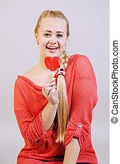 blonde woman holding a lollipop