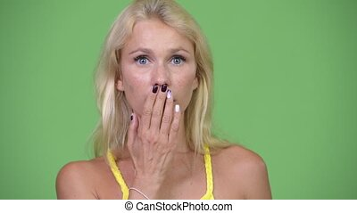 Young beautiful blonde woman looking shocked while covering mouth