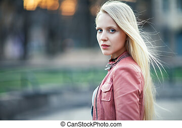 Young beautiful blonde woman portrait posing in city street on sunset