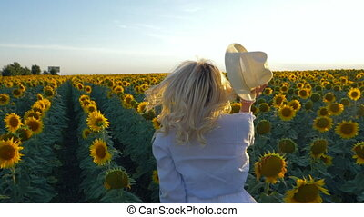 Young beautiful blonde woman running in sunflower field. Sunset background. Sexy sensual portrait of girl in flower wreath and white summer dress. Slow motion.