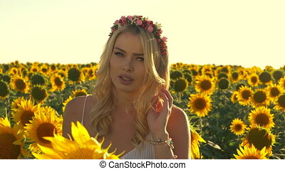 Young beautiful blonde woman standing in sunflower field. Sunset background. Sexy sensual portrait of girl in flower wreath and white summer dress. Slow motion.