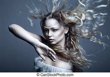 Portrait of young, beautiful and emotional blonde woman with blowing hair