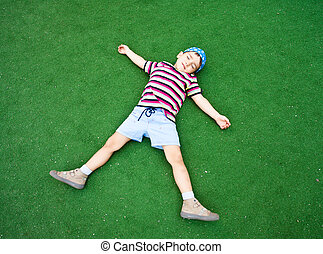 boy laying on plastic green grass