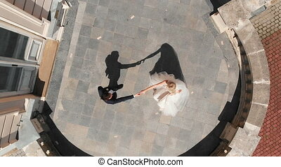 Young beautiful bride and groom dancing first dance on the...