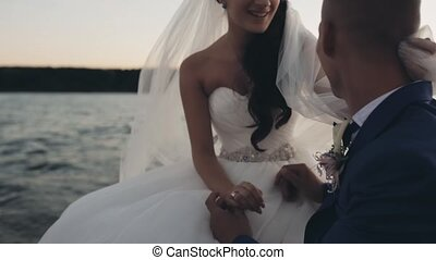 Young beautiful bride and groom sailing on the wind. Happy newlyweds sit on board of the yacht and talking on sunset.