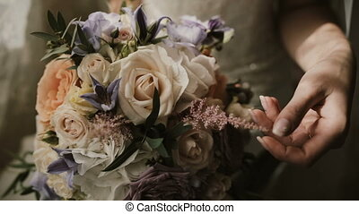 Young beautiful bride holding the wedding bouquet. Close-up view of female touching the flowers before ceremony.