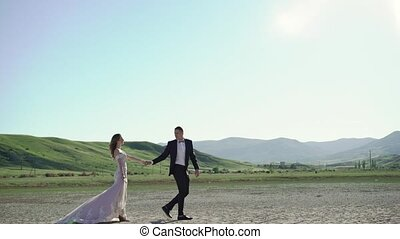 Young beautiful bride in a wedding dress and groom walking