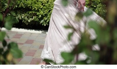 Young beautiful bride in a wedding dress goes to the groom. Meeting of the newlyweds.