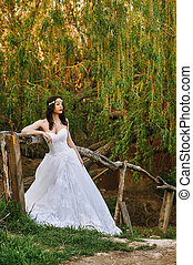Young beautiful bride in the flowered garden . Wedding day