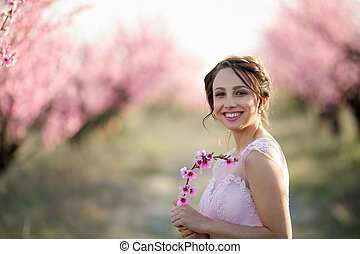 Young beautiful bride in the flowered garden.
