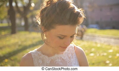 young beautiful bride standing in the park  and straightens hair shot in slow motion  close up