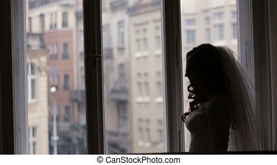 Young beautiful bride staying near the window and waiting for her groom at home.
