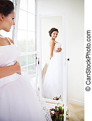 Young beautiful bride to be trying her dress in shop