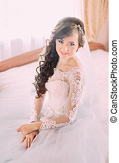 Young beautiful bride with long curly hair sitting in his bedroom at edge of the bed and smiling
