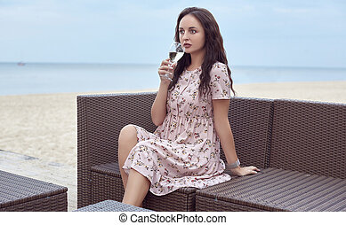 Young beautiful bright girl in a summer dress sitting on the beach