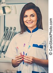 Young beautiful brunette female dentist with three toothbrushes at dentist's surgery