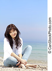 Young beautiful brunette girl at the beach in spring time. Outdoor photo.