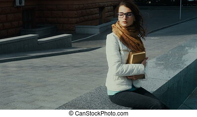 young beautiful brunette girl in glasses with books in hands...