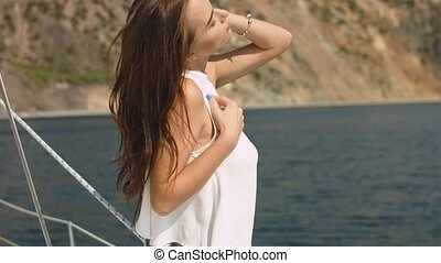 Young beautiful brunette girl on the luxury yacht