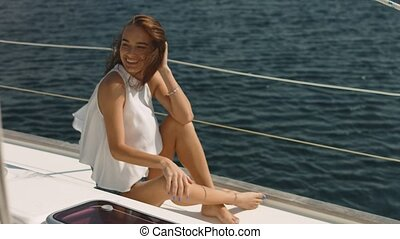 Young beautiful brunette girl sitting on the luxury yacht