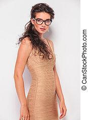 brunette wearing glasses while posing in studio