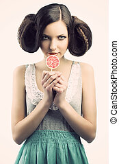 young beautiful brunette with a creative luxury hair style and a colored lollipop. She is in front of the camera, looks in to the lens with an a sly expression and takes the lollipo near the mouth