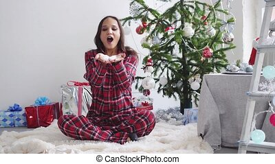 Young beautiful brunette woman blowing confetti by fir-christmas tree and the window in studio. slow motion. 3840x2160