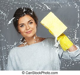Young beautiful brunette woman cleaning window glass