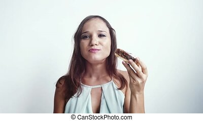 Young beautiful brunette woman eats a delicious cake on a white background. slow motion. 3840x2160