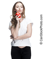young beautiful brunette woman holding red pepper