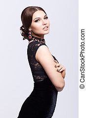 Young beautiful brunette woman in black dress