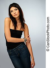 Young beautiful brunette woman in black top and jeans isolated on grey background