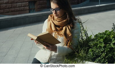 young beautiful brunette woman in glasses reading a book