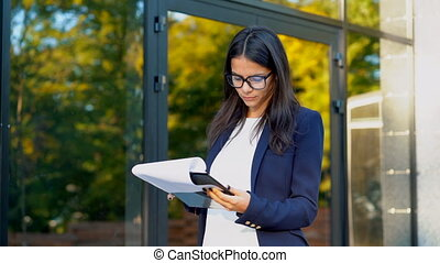 Young beautiful brunette woman in suit and glasses checks documents, utility bills, report. Businesswoman standing near office building. She is satisfied with the work of staff