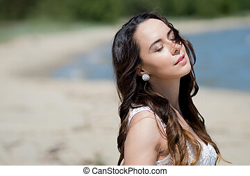 Young beautiful brunette woman in white dress on the seashore. portrait with closed eyes