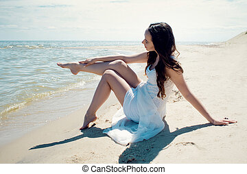 Young beautiful brunette woman in white dress on the seashore. Stroking a leg with a hand