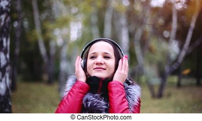 Young beautiful brunette woman listening music in headphones in autumn park. 1920x1080