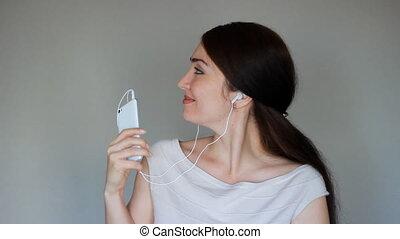 Young beautiful brunette woman listening to music on headphones on the phone, smiling and dancing. The concept of music, songs