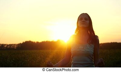 Young beautiful brunette woman meditates in the field during amazing sunset with sun flare effects.