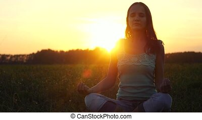 Young beautiful brunette woman meditates in nature, in the field during amazing sunset. 3840x2160