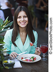 Young beautiful brunette woman ?sitting in a restaurant